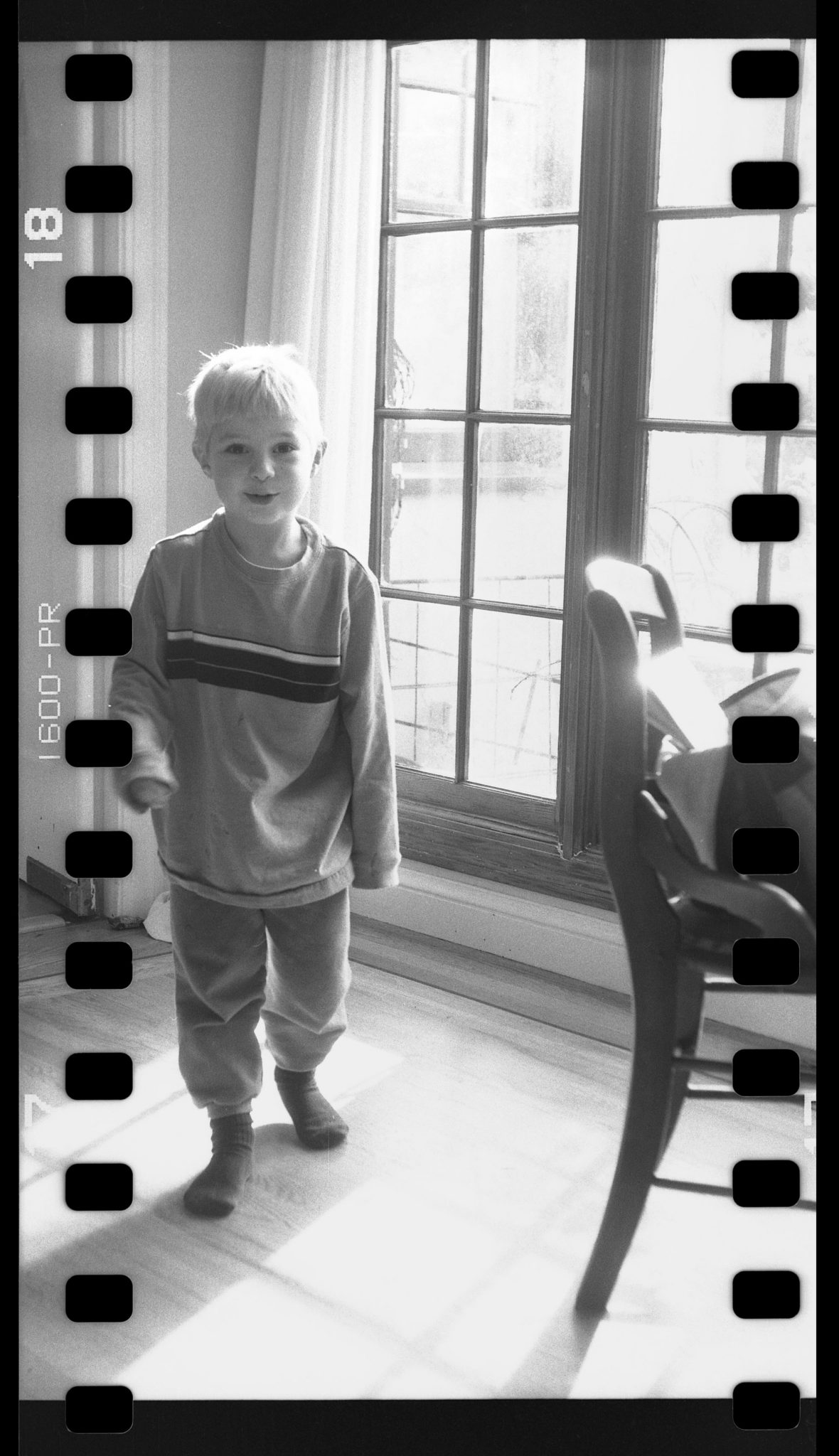 Sprocket hole photo of Max by the windows of the Beaver St house
